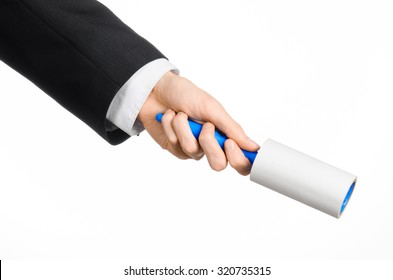 Dry cleaning and business theme: a man in a black suit holding a blue sticky brush for cleaning clothes and furniture from dust isolated on white background in studio.