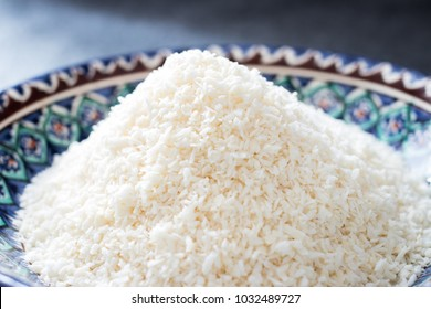 Dry coconut meat in asian plate. Indian traditional tropical fruit used as spice for sweets and cooking. Raw, vegan, vegetarian healthy food concept.