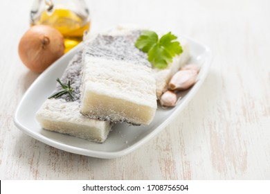 dry cod fish on white dish on old white wooden background