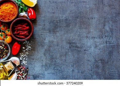 Dry colorful spices in bowls with fresh seasoning and healthy vegetables on dark rustic background, top view, border. Vegetarian or diet food concept