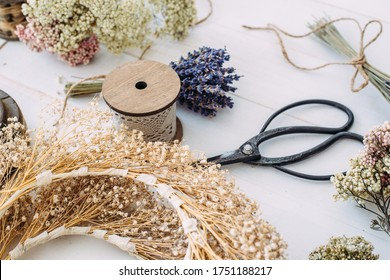 Dry compositions and bouquets of flowers and plants for the interior lie on a white wooden table. Flat lay.