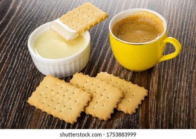 Dry cookie on small white bowl with condensed milk, yellow cup with coffee espresso, cookies on dark wooden table