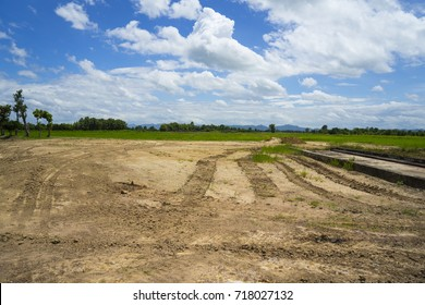 Dry crack red and sticky soil from swamp dredging or digging, reclamation land area prepare for house construction in rural area with wide blue sky and fresh air, North of Thailand