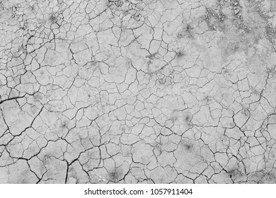 Dry and cracked soil ground during drought, viewed from above in black and white.