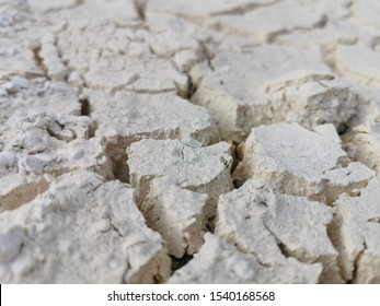 Dry desert clay floor cracked due to summer and drought.Cracked ground or mud cracks on earth surface background.