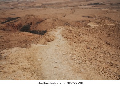 Dry desert hiking trail on the mountain slope. Panoramic view of Negev desert in Israel.