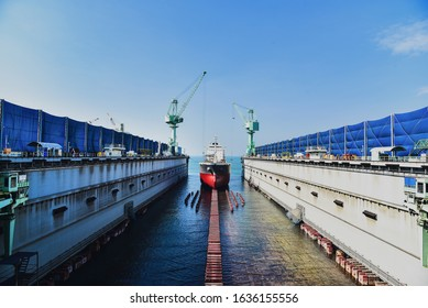 Dry dock with Cargo Ship maintenance or repair at floating dock in shipyard both deck crane loading during bring ship in to the dry dock. - Shutterstock ID 1636155556