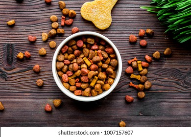 dry dog food in bowl on wooden background top view
