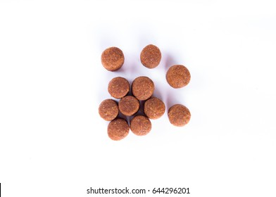 Dry dog food granules isolated on white background top view