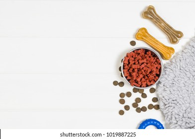 Dry dog pet food in bowl and accessories on white wooden background top view. Pet feeding and care concept backgrounds with copy space. Photograph taken from above.