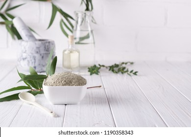 Dry facial clay powder in bowl. Natural cosmetics for home or salon spa treatment on white background