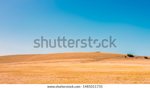 Dry fields, hills and blue sky landscape