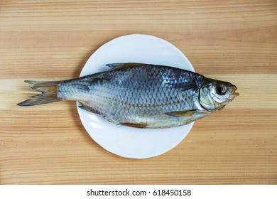 Dry fish on a white plate on a wooden board