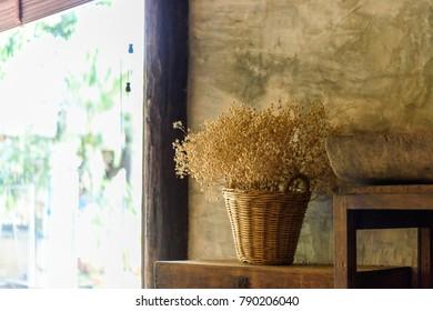 dry flower in basket beside the wall