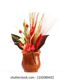 Dry flowers in a broken ceramic vase on white background