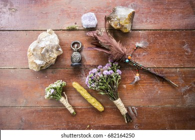 Dry flowers, a thistle, a staff of feathers, a crystal of quartzite and candles made from natural wax, witchcraft, spells, magic, Wicca, the goddess