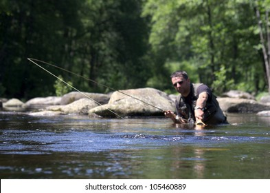 Dry fly fishing. Fly fishermen in a French trout river. Fisherman fight against a big trout
