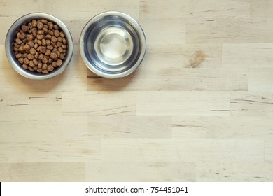 Dry food for cats. Two bowls. Wooden surface. Two bowls. With a dry food and another with water inside. Surface of light wood. View from above.