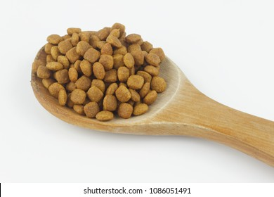 Dry food or one colored kibble on spatula. Isolated white background