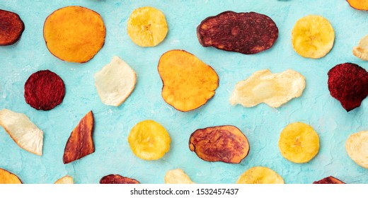 Dry fruit and vegetable chips, panoramic overhead shot. Healthy vegan snack, an organic food flat lay on a blue background texture
