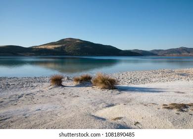 dry grass and white sand on coast of beautiful calm lake, salda golu, turkey