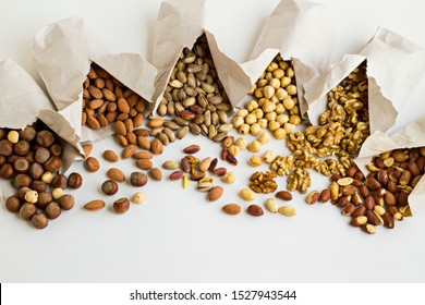 Dry, group of shelled nuts with hazelnut,almond,pistachio,walnut and peanuts,spilled from teared paper bags,on the white surface with copy space