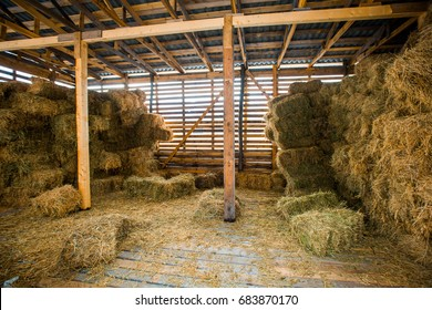 Dry hay stacks in rural wooden barn interior on the farm