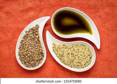 dry hemp seeds, hearts and oil in small teardrop bowls against red textured bark paper