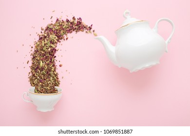 Dry herbal tea pouring from white porcelain teapot into cup on pink surface. Flat lay. Tea time concept.