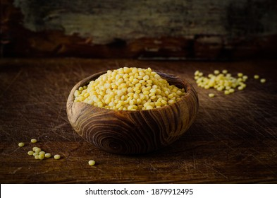 Dry Israeli couscous ptitim in a wooden bowl on wooden table. Uncooked ptitim pasta. Selective focus. Toned image. Rustic style - Shutterstock ID 1879912495