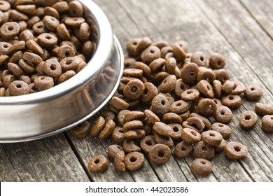 Dry kibble dog food in bowl on old wooden table.