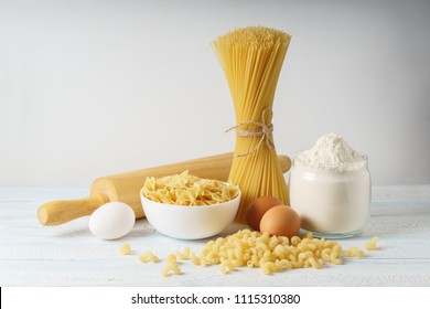 Dry kind's of pasta with spaghetti and ingredients for pasta on white wood background.