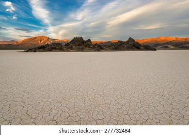Dry lake bed on sunset, with cracked mud on a lake floor blue sky, clouds and mountains. Racetrack Playa. Death Valley national park. California. USA.