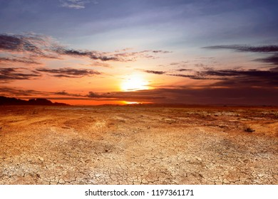 Dry land with cracked ground and dramatic sky at sunset
