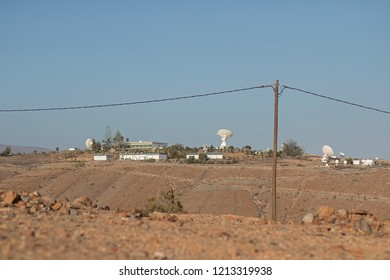Dry landscape with electric cable and a parabolic antenna.