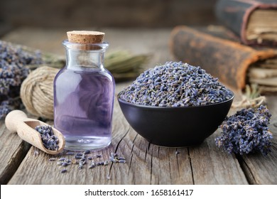 Dry lavender flowers in bowl and bottle of essential lavender oil or infused water. Old books and lavender flowers bunch on background.