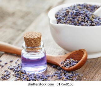 Dry lavender flowers in mortar and bottle of essential oil. Selective focus.