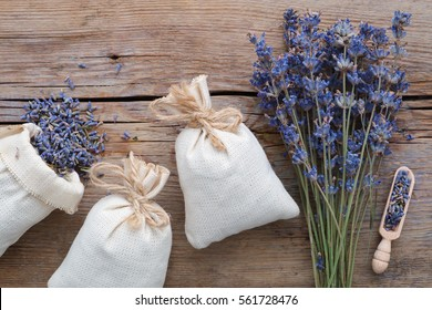 Dry lavender flowers and sachets on wooden background. Top view. Flat lay.
