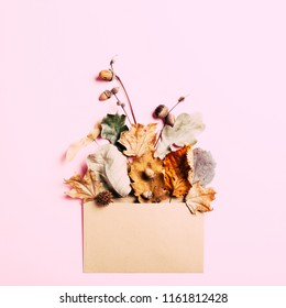 Dry leaves in kraft envelop on pink background. Autumn concept card.