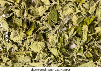 The dry leaves of lemon balm on white table. Conceptual abstract background