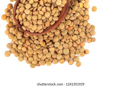 dry lentils on wooden spoon isolated on a white background.