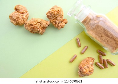 Dry maca roots and capsules,maca powder on green background