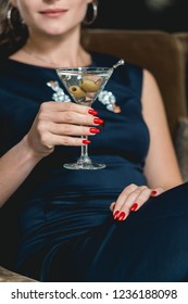 Dry Martini cocktail in womans hands with red manicure. Luxery hotel lobby bar.