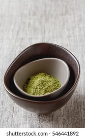 Dry Matcha tea in a small plate. Grey wood background