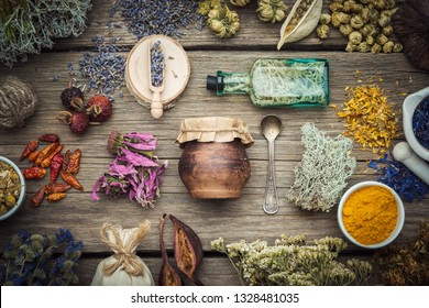 Dry medicinal herbs, plants, roots, ingredients for making of herbal medicine drugs, bottle of infusion, jar of ointment, mortar on wooden background.