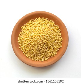 Dry millet grains in clay brown bowl isolated on white. Bowl of millet, organic millet seeds, closeup.