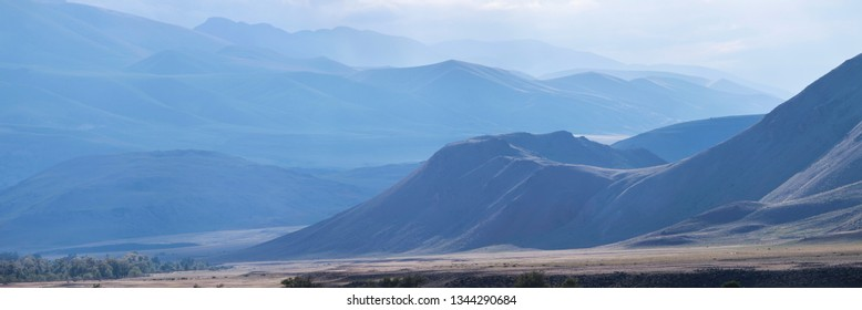 Dry Mongolian landscapes in the Altay Mountains, blue natural background. Panoramic view of the mountains in the morning haze.
