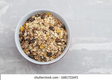 dry muesli in the bowl on ceramic background
