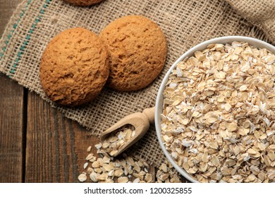 Dry oatmeal and oatmeal cookies in a white bowl and a wooden spoon. food. healthy food. on a brown wooden table.