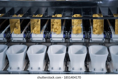Dry pasta on automatic combination weighers. Multihead weighers machine in food industry.